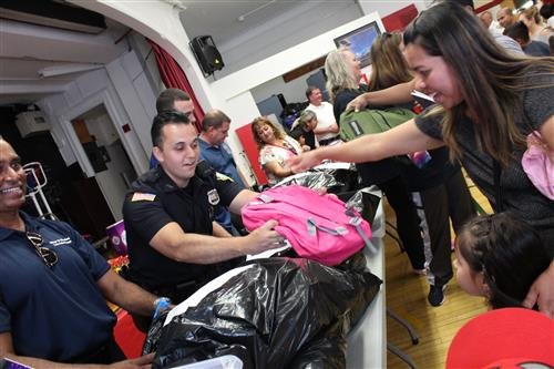 Police officer hands out backpack